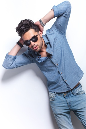 stile: casual giovane uomo in posa con le mani dietro la testa, mentre guardando la telecamera. su sfondo grigio Archivio Fotografico