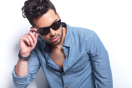 closeup of a casual young man holding a hand on his sunglasses while looking away from the camera. on gray background Stock Photo