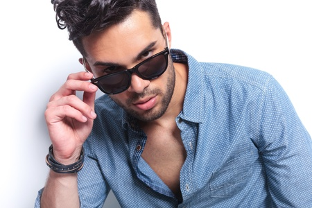 closeup of a casual young man with his sunglasses pulled down, looking at the camera with a serious expression. on gray background photo