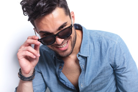 closeup of a casual young man taking off his sunglasses and smiling for the camera. on gray background photo