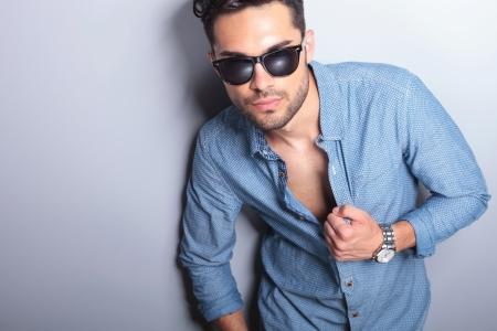 homem: entalhe retrato de um jovem casual com a mão na sua camisa desabotoada olhando para a câmera. no fundo cinzento