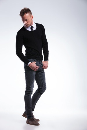 full length picture of a casual young man with his thumbs in his pockets looking down, behind him, away from the camera. on light gray studio background Stock Photo - 20999735