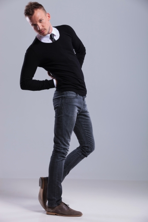 full length picture of a casual young man twisting his body and holding his hands at his back while looking at the camera. on light gray studio background