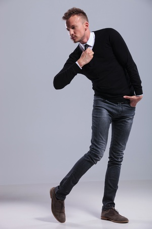 knees bent: full length picture of a casual young man posing crooked while fixing his tie and looking away from the camera. on gray studio background