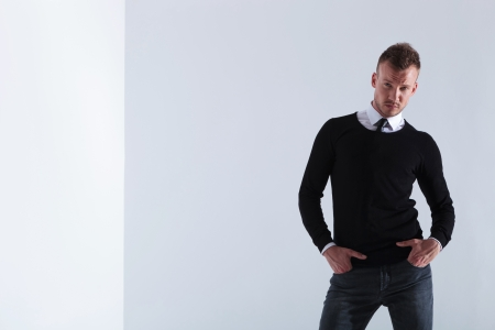 pullover: casual young man holding both hands in his pockets and looking into the camera. on light gray studio background Stock Photo