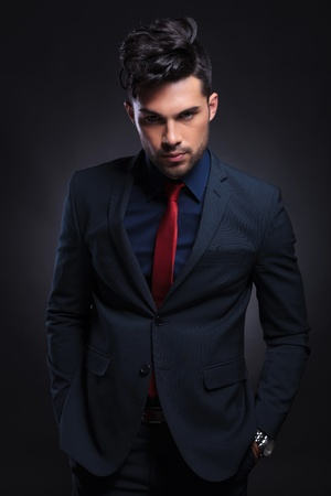 elegant business man: young business man standing with both hands in pockets and looking at the camera. on a black background