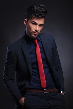 lazo negro: Hombre de negocios joven con las manos en los bolsillos mientras mira a la cámara. sobre un fondo negro