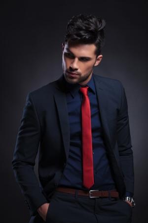 галстук: молодой деловой человек смотрит в сторону от камеры, держа руки в карманах. на черном фоне Фото со стока