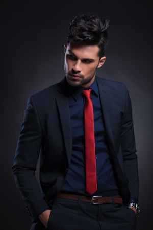 suit tie: young business man looking away from the camera while holding his hands in his pockets. on a black background