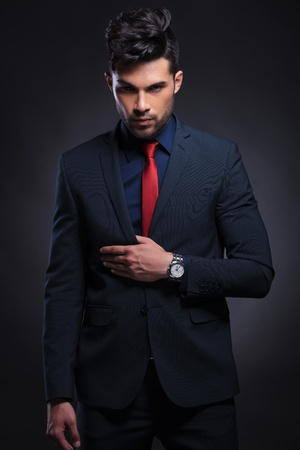 hair tie: young business man holding his thumb inside his suit jacket while looking at the camera. on a black background