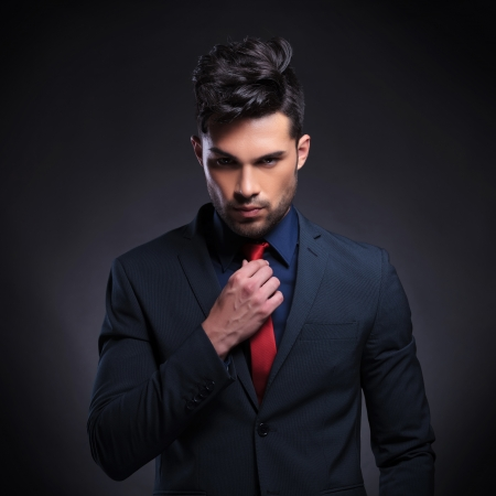 crooked: portrait of a young business man looking at the camera while fixing his tie. on a black background Stock Photo