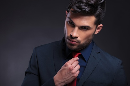 adjusting: young business man adjusting his tie while looking at the camera. on a black background