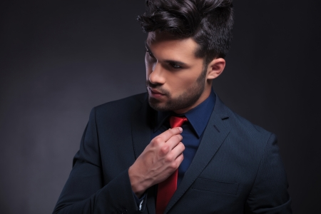 hair tie: closeup portrait of a young business man adjusting his tie and looking away from the camera. on a black background