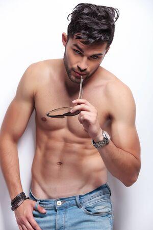 seins nus: jeune homme torse nu mordant ses lunettes de soleil tout en regardant la cam�ra. sur fond gris clair Banque d'images