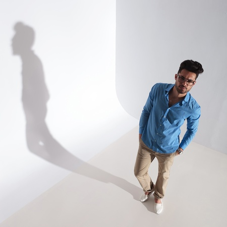 full length upper view picture of a casual young man looking up at the camera while holding his hands in his pockets. on light gray background with shadow photo