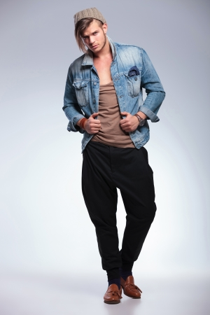 lapels: full length portrait of a casual young man holding both hands on his jeans jacket while looking at the camera. on gray studio background