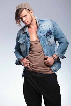 lapels: casual young man holding his hands on his jeans jacket while looking at the camera. on gray studio background Stock Photo