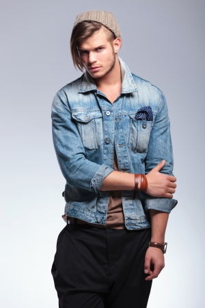 long pants: casual young man holding his elbow while looking at the camera. on gray studio background Stock Photo