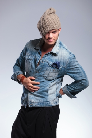 casual young man holding his hand on his belly and his cap pulled down while looking at the camera. on gray studio background photo