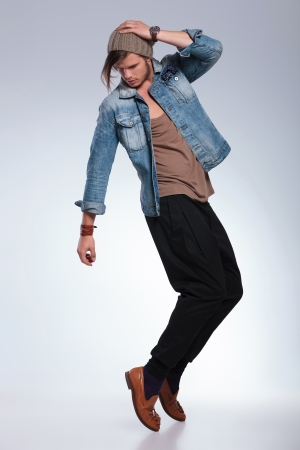 man looking down: full length portrait of a casual young man balancing on his toes while looking down and holding his hand on his head. on gray studio background Stock Photo