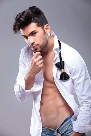 six pack abs: sexy casual young man with unbuttoned shirt touching his chin and looking at the camera. on gray background Stock Photo