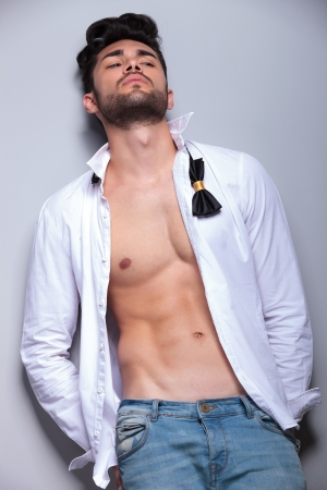 unbuttoned: sexy casual young man leaning back and looking away from the camera while holding his hands in his back pockets. on gray background Stock Photo