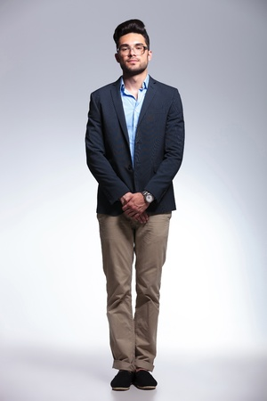 crotch: A casual young man holding his hands together in front and looking at the camera with a serious expression. on gray background Stock Photo