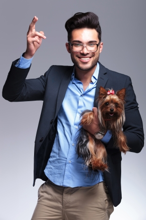 casual young man holding a puppy and making a shooting gesture with his hand while smiling for the camera. on gray background Stock Photo - 21690231