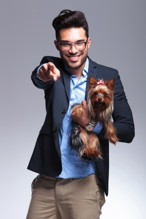 casual young man holding a puppy and pointing at the camera with a smile on his face. on gray background Stock Photo - 21690257