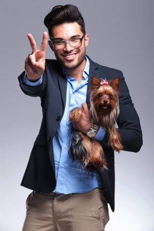 geeky: casual young man holding a puppy and showing the victory sign while smiling for the camera. on gray background Stock Photo