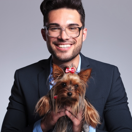 geeky: casual young man holding a puppy in his hands while looking at the camera and smiling. on gray background