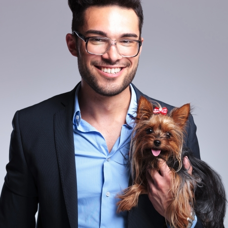 geeky: casual young man holding a puppy and looking at the camera with a smile on his face. on gray background