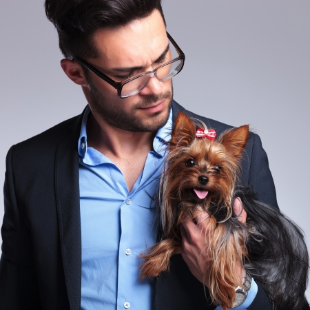 geeky: casual young man holding a puppy and looking at it. on gray background Stock Photo
