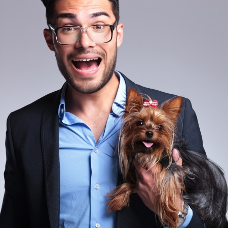 casual young man holding a puppy and looking surprised into the camera. on gray background Stock Photo - 21690415