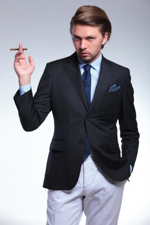 stylishly: young business man stylishly holding a cigarette while looking at the camera with his other hand in pocket. on a gray background