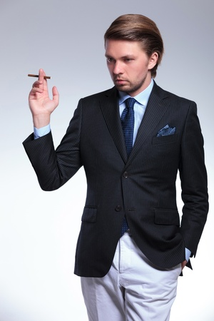 young sylish business man holding a cigarette and a hand in his pocket while looking down, away from the camera. on a gray background photo