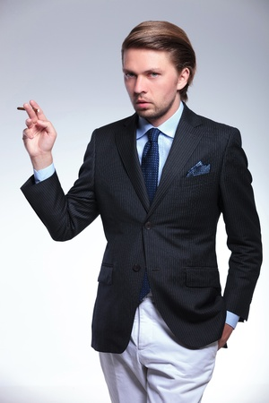 hand in pocket: young business man holding a hand in his pocket and a cigarette to his side with style. on a gray background Stock Photo