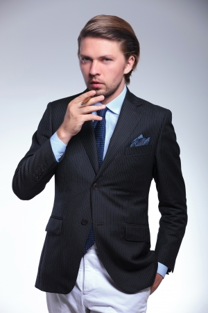 habbit: young business man holding a cigarette and his hand in his pocket while looking at the camera. on a gray background Stock Photo