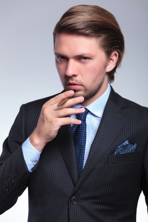 closeup of a young business man with a cigarette at his mouth, looking at the camera. on a gray background photo