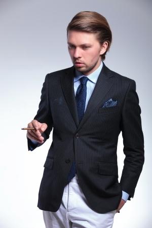 young business man looking down while holding a hand in his pocket and a cigarette in the other. on a gray background photo