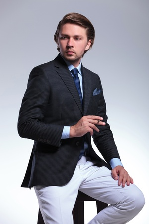 young business man sitting on a stool with a cigarette in his hands and looking away from the camera. on a gray background photo