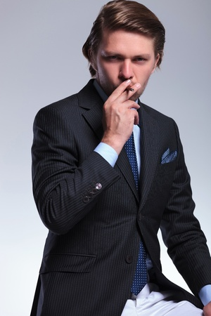 habbit: young business man smoking while looking at the camera. on a gray background