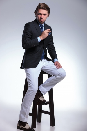 full length picture of a young business man sitting on a high stool and looking at the camera with a cigarette in his hand. on a gray background photo