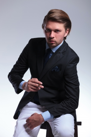 habbit: young business man on a chair leaning forward with a cigarette in his hand while looking at the camera. on a gray background