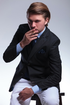 habbit: young business man seated on a chair is smoking a cigarette while looking at the camera. on a gray background
