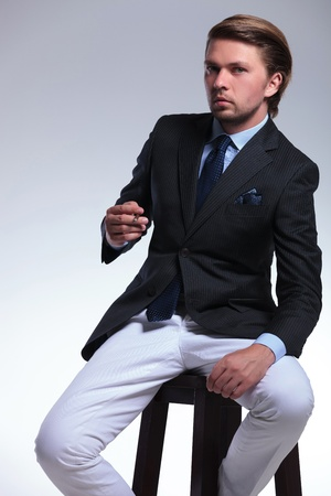 young business man sitting on a chair with a cigarette in his hands and looking at the camera. on a gray background photo