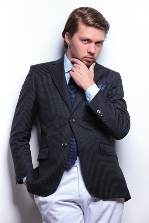 young business man holding a hand at his chin and the other in his pocket while looking at the camera. on a light gray background photo