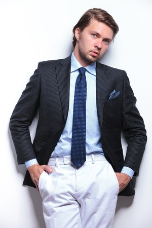 young business man with unbuttoned suit jacket and hands in pockets leaning on the wall behind him and looking at the camera. on a light gray background photo