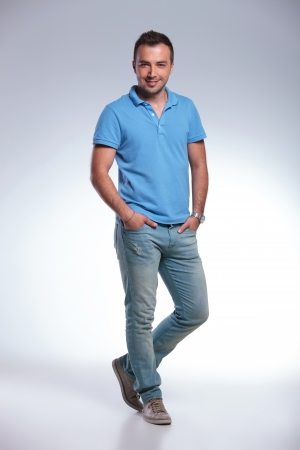 standing: A young casual man standing with both hands in pockets and smiling for the camera. on gray background Stock Photo