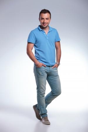 ni�o parado: Un casual hombre joven de pie con las dos manos en los bolsillos y sonriendo para la c�mara. sobre fondo gris